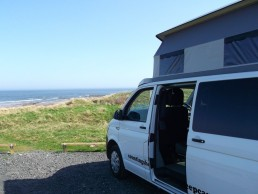 side view sandy at beach camper van hire